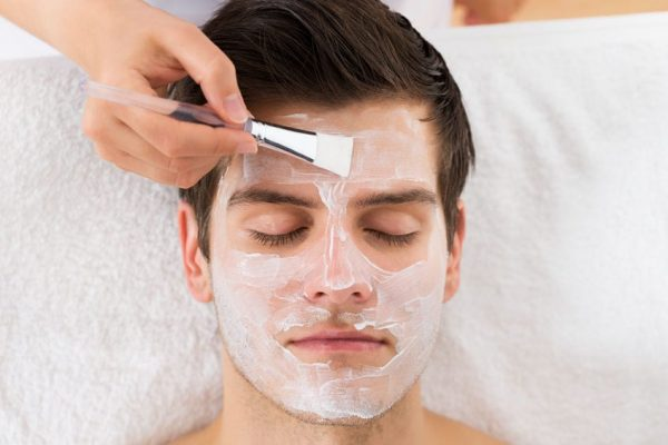44592084 - therapist hands with brush applying face mask to a young man in a spa